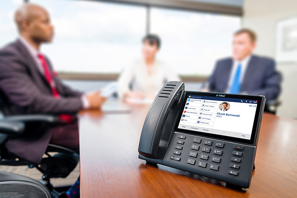Mitel business telephone system handset in an office meeting room